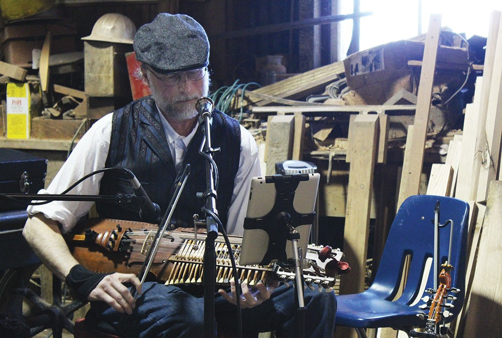 Sam McNeill of Good Company, mixing the ancient and the modern — playing a solo set of traditional Swedish music on a nyckelharpa and reading the tunes from his iPad — at the May 3 Blue Ox May Day Living History and Artisan Fair. - PHOTOS BY BOB DORAN