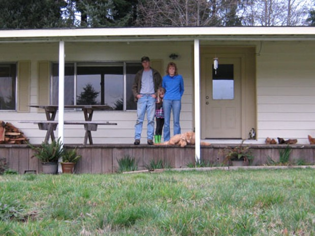 Scott and Linda Powell with their daughter and the family dog on the porch of their Dow's Prairie Mobile Home. - PHOTO COURTESY OF THE PACIFIC LEGAL FOUNDATION