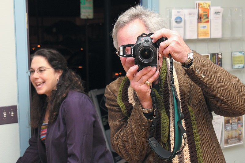 """Shutterbug Rick St. Charles turns the tables on the paparazzi at an Arts Alive! opening at MikkiMoves. That's Michelle """"Mikki"""" Cardoza photobombing the shot."""