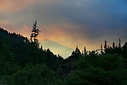 Smoke from the Jake and Portuguese fires hangs in the air over the Salmon River road at dusk. Photo by Yulia Weeks