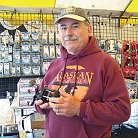 Two If By Sea Sport fisherman Michael Holland, of Eureka, checks out a new reel at the big sale at Englund's. In the end, he got an inflatable life vest. Photo by Heidi Walters