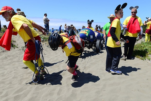 Team Melvin crew pull ropes while the pilots peddle to ascend the dune that leads to Deadman's Drop. - MARK MCKENNA