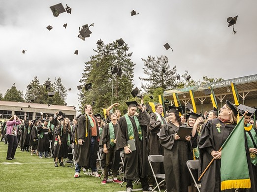 The tradition continues – graduates toss their mortarboard hats in the air to celebrate graduating after the Arts, Humanities & Social Sciences Commencement 2015 at Humboldt State University on Saturday, May 16. - MARK LARSON