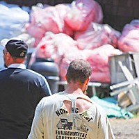 After Hacker Creek Tired and battered contractors face a mound of absorbent pillows waiting to be placed in the creek. Photo by Kym Kemp.