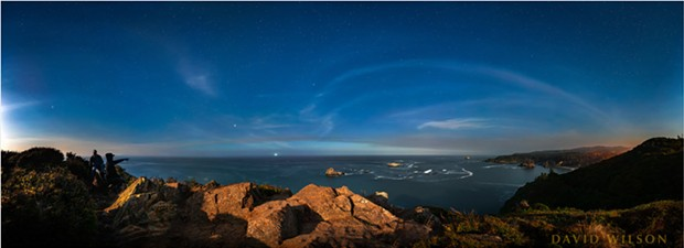 Encompassing a greater than 180 degree field of view, this panoramic image was photographed from the top of a rock outcrop on the west edge of Trinidad Head. Straight ahead is west, while to right and left the view is to the north and south, respectively. Looking north you can see College Cove, with the warm glow of Trinidad coming in from the right edge. On the left, hidden behind the human figures, lie the towns of McKinleyville, Arcata and Eureka. - DAVID WILSON