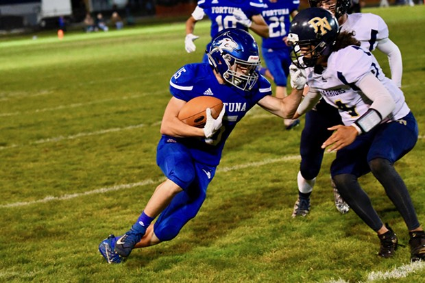 Fortuna High School Husky Levi Nyberg carries the ball for big - yardage in front of a homecoming crowd against the previously unbeaten Del Norte Warriors. Fortuna won the Friday night game, 62-32. - JOSE QUEZADA