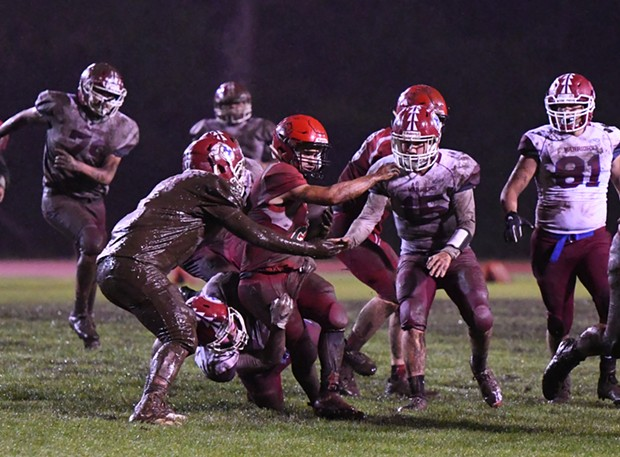 McKinleyville Panther running back Caleb Martinez is swarmed by Hoopa Warrior defenders. It was a wet and muddy affair as the Warriors took advantage of a slick field to pound out a win over the homecoming-celebrating McKinleyville Panthers 22-12 Saturday night. - CANDICE LACKEY