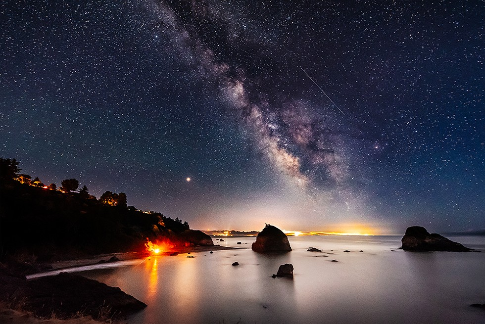Looking south from Tepona Point during the Perseid meteor shower, August of 2018. The bonfire of a group of Perseid meteor gazers blazed on the curve of Houda Point Beach, a beautifully warm counterpoint to the stars and planets above. - PHOTO B Y DAVID WILSON