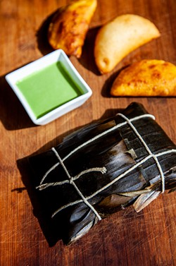 Hallaca, Venezuelan tamale wrapped in banana leaf and arepitas. - AMY KUMLER