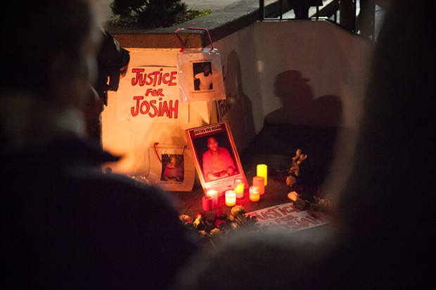 A Justice for Josiah sign and posters of Lawson illuminated by candlelight at the vigil. - MARK MCKENNA