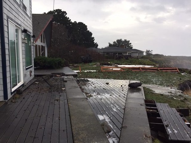 A fence was knocked down between these two waterfront homes and waves left debris on deck of the home in the foreground. - CHERYL ANTONY OF SHELTER COVE FIRE