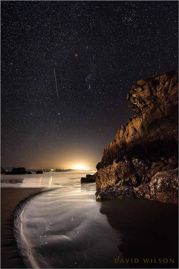 Lights from shore illuminate this great chunk of rock here where the wild coastline intersects with humanity. Above, a satellite's eye in the sky so high crawled slowly past Orion. Humboldt County, California. February 22, 2019. - DAVID WILSON