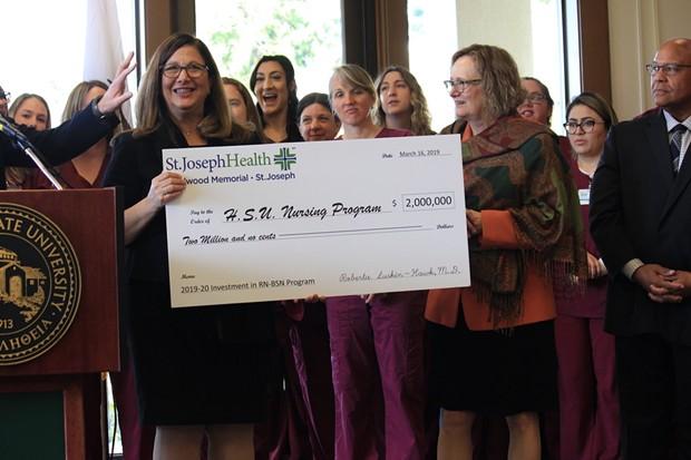 Humboldt State University President Lisa Rossbacher (right) receives a $2 million check from St. Joseph Hospital for the university's new nursing program. - FREDDY BREWSTER