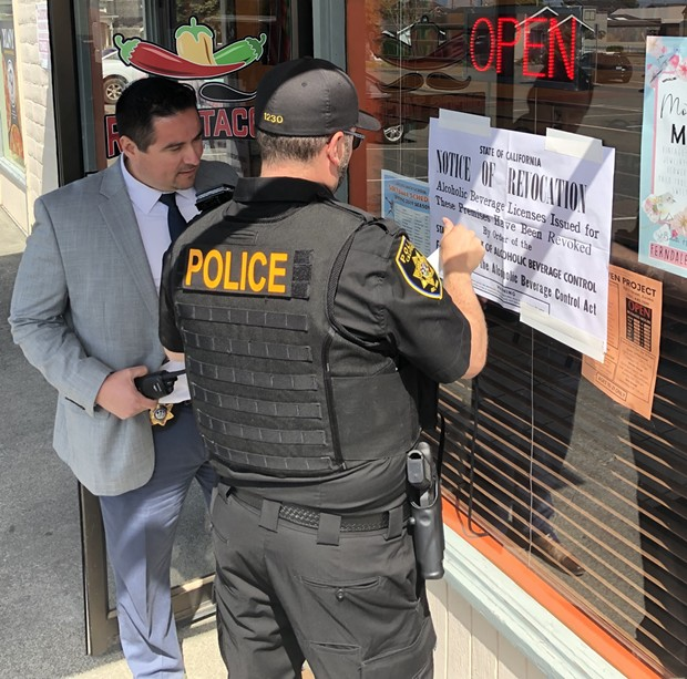 An agent with the California Department of Alcoholic Beverage Control posts a notice of revocation at Rico's Tacos. - SUBMITTED