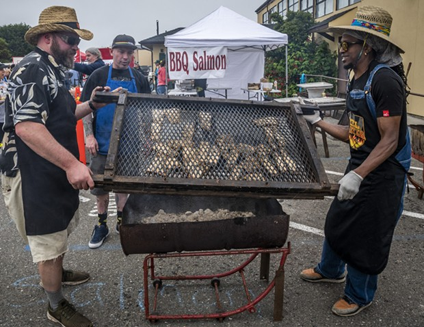 Pitmaster John McClurg (Left) and volunteers Ryan (middle) and Gilbert helped wrangle the grilled salmon. - PHOTO BY MARK LARSON