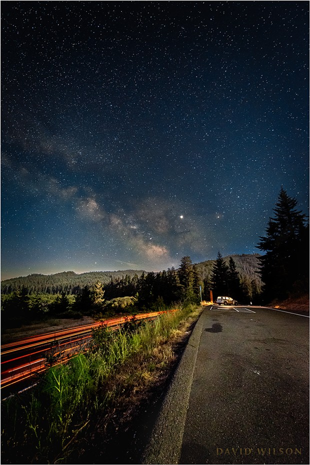 Streaks of humanity pierce the night even as the half moon bathes the forested landscape in its soothing luminance. At the far end a fellow traveler of the night sheltered in their car's bubble of light. Vista Point, Humboldt County, California. - DAVID WILSON