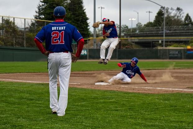 Ryan Higgins slides under a floating third baseman on Friday evening. - MATT FILAR