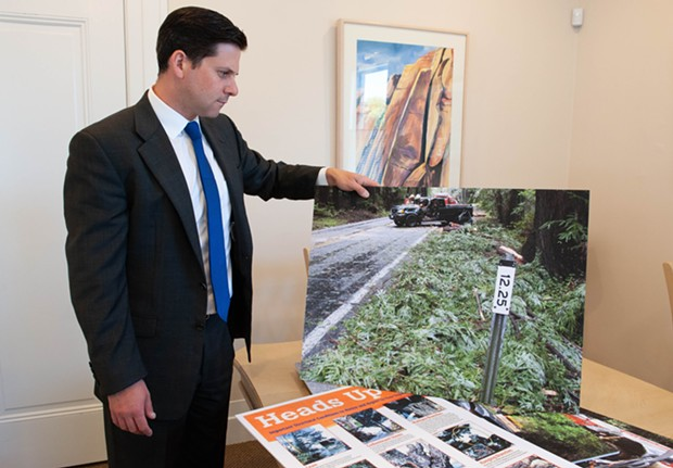 Attorney Ben Mainzer with a photograph of the crash scene. - MARK MCKENNA