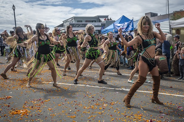 The flower blossom-strewn east side of the Arcata Plaza made a good dance platform for the Samba da Alegria dancers. - PHOTO BY MARK LARSON
