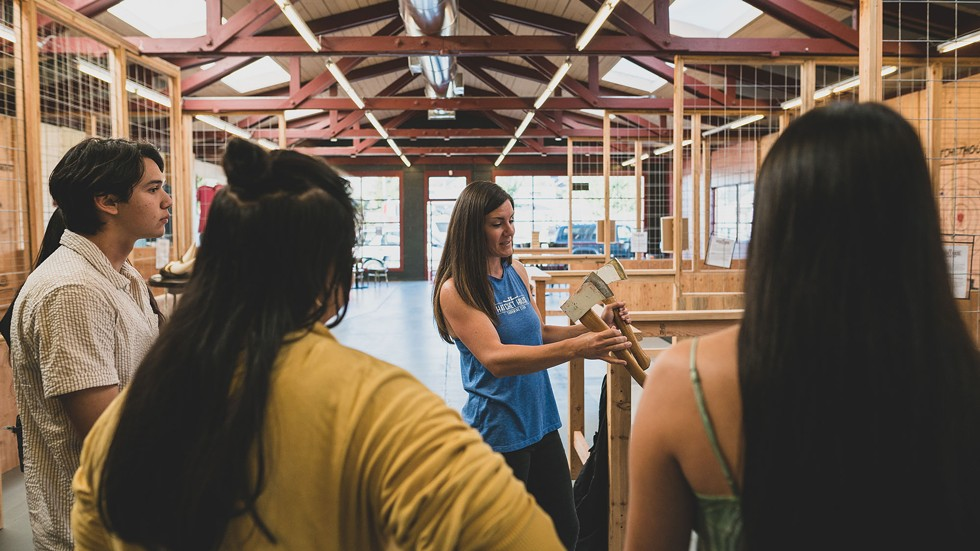 Lauren Fischer shows newbies the basics of ax-throwing. - CONNOR RAY PHOTOGRAPHY