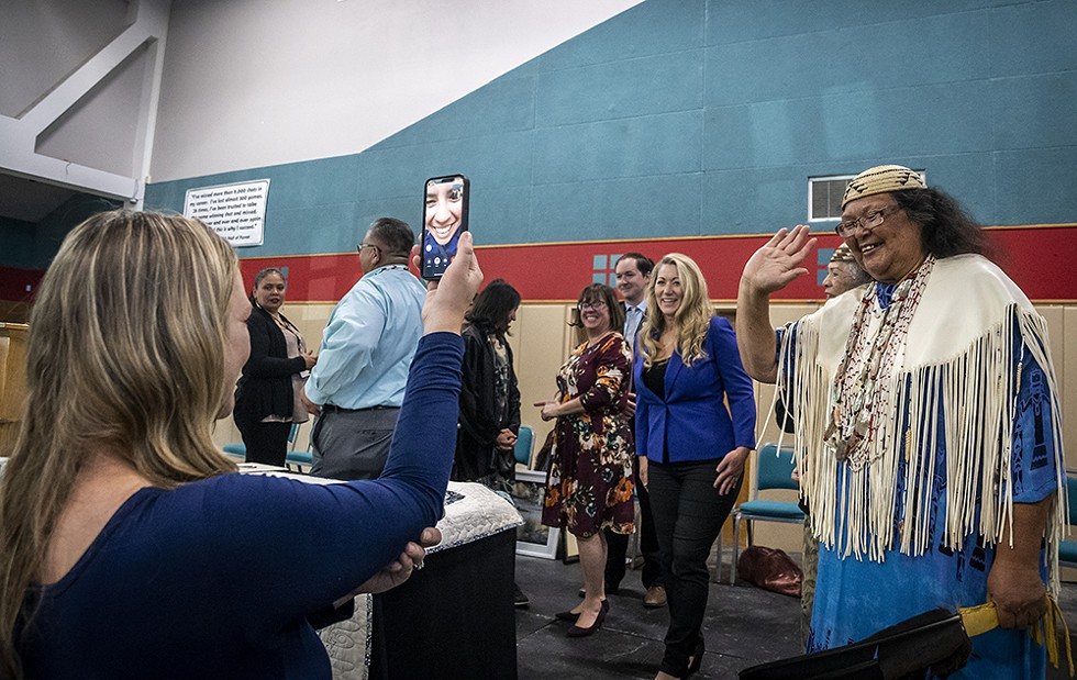 Wiyot tribal elder Cheryl Seidner (right) waves hello to Eureka City Councilmember Natalie Arroyo, who was watching the ceremony via Facetime (with a little help from Eureka Executive Assistant Christine Tyson) while deployed on active duty orders with the U.S. Coast Guard in Georgia. - BY MARK LARSON