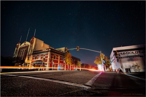 All city lights were out in Eureka, California, during PG&E's Public Safety Power Shutoff on October 27, 2019. The headlights of a few passing cars illuminated the scene, leaving trailing streaks from their taillights. 4th & G Streets, Eureka. - DAVID WILSON