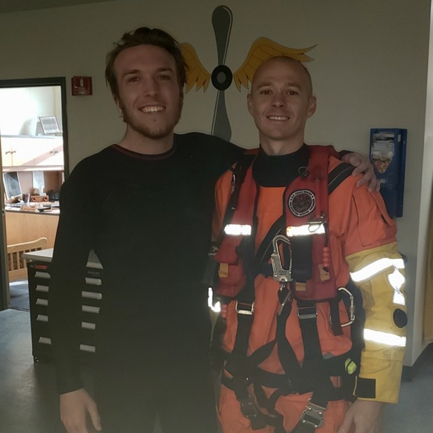 Petty Officer 2nd Class Michael Hernon, a Coast Guard Sector Humboldt Bay rescue swimmer, stands with Kris Nagel, a distressed surfer who was rescued by the Coast Guard when he was reportedly swept toward rocks near Moonstone Beach while he was surfing, Dec. 15, 2019. A Sector Humboldt Bay MH-65 Dolphin helicopter crew was dispatched to the scene, hoisted Nagel into the helicopter and took him to California Redwood Coast - Humboldt County Airport where he was transferred to emergency medical services personnel. - COURTESY OF THE U.S. COAST GUARD SECTOR HUMBOLDT BAY