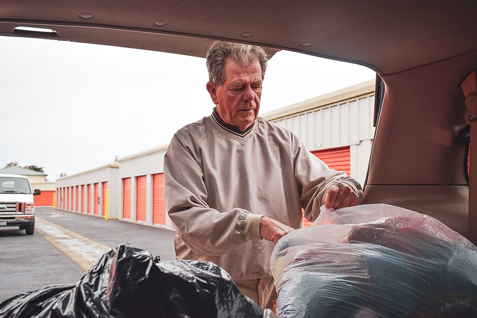 Robert Lohn pulls bags of coats from the back of his minivan - PHOTO BY THADEUS GREENSON