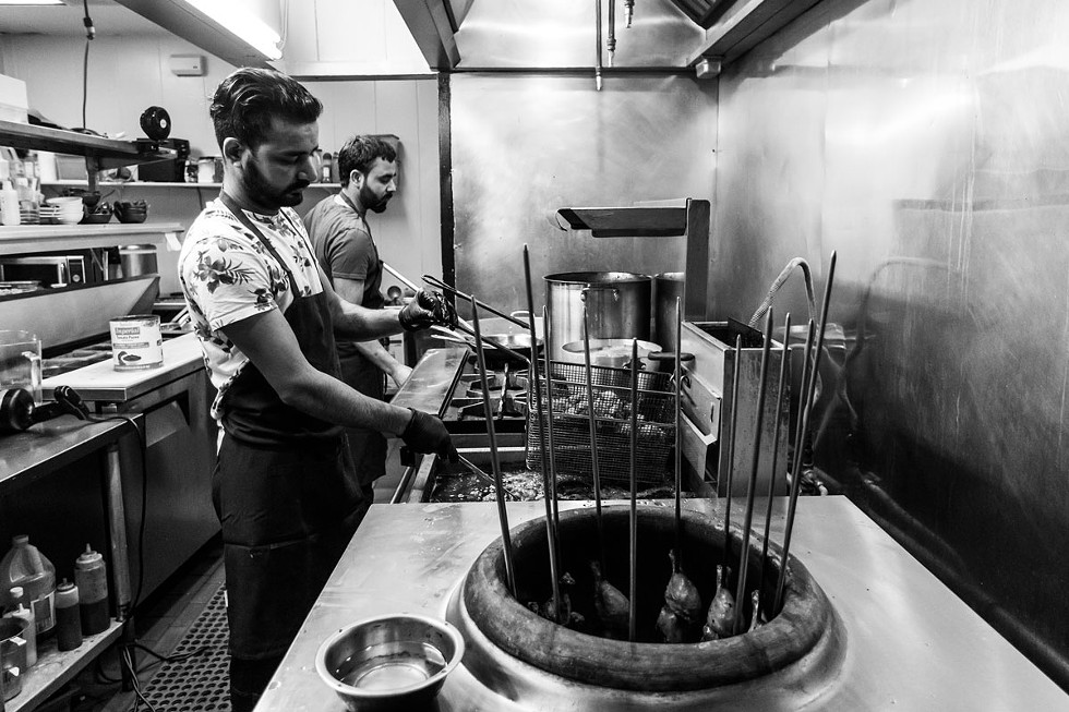 Gurpinder Singh manages the fryer and tandoor, while chef Dalbir Singh cooks a pot of curry. - AMY KUMLER