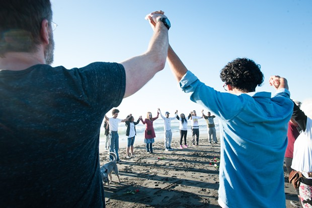 Following Charmaine Lawson's lead, attendees at a vigil raised their hands in memory of David Josiah Lawson. - MARK MCKENNA