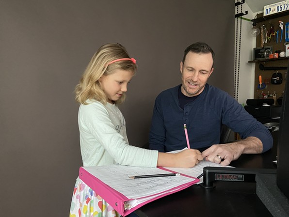 """With her school closed by the coronavirus pandemic, Ray Ortega, a podcaster in East Sacramento, conducts math class for his daughter, Linden, before dismissing her for """"recess"""" on Wednesday, March 18, 2020. - PHOTO BY SHARYN ORTEGA FOR CALMATTERS"""