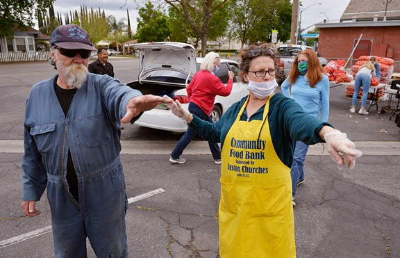 Victoria Salwasser, right, directs Curtis Smith, left, as volunteers distribute food to families in cars at a food bank giveaway held at Easton Presbyterian Church Monday, April 6, 2020 in Easton. - ERIC PAUL ZAMORA, THE FRESNO BEE
