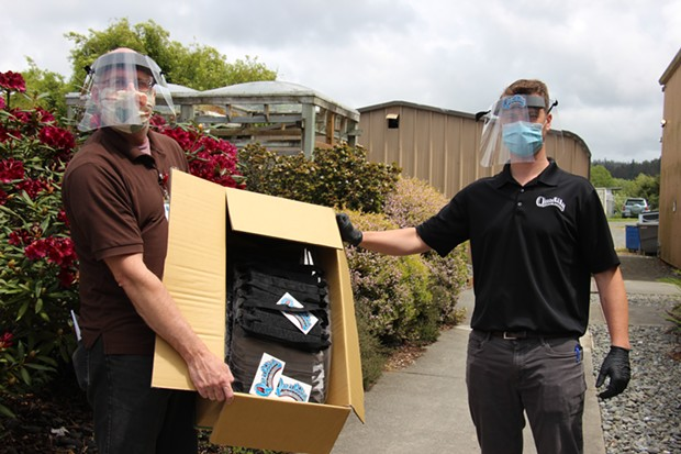 Ross Creech (r) of Quality Body Works in Eureka presented 100 face shields to Mad River Community Hospital representative Ron Alexander (l) of the Materials Management department. - MAD RIVER HOSPITAL