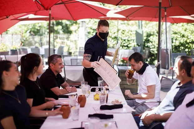"""Cleverson Davis, a waiter at Palermo Italian Restaurant in San Jose, tends to customers on June 5, 2020. Outdoor parts of restaurants can remain open in the state's 19 """"watch list"""" counties. - PHOTO BY DAI SUGANO, BAY AREA NEWS GROUP"""