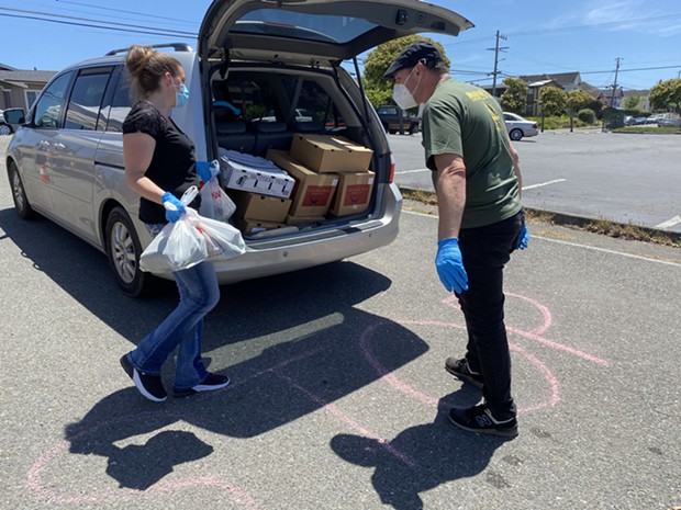 Volunteers load food into the trunk of a waiting car at a recent food distribution. - SUBMITTED
