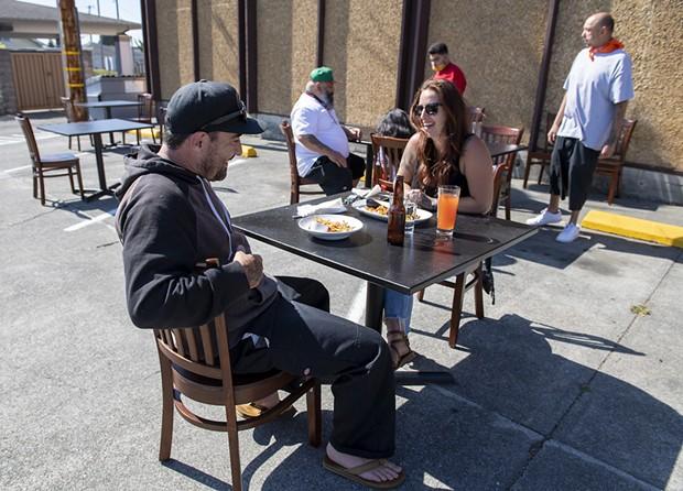 Head chef of Five Eleven Josh Wiley and his girlfriend Cheyanne Samson enjoyed empanadas int the ersatz parking lot cafe. - PHOTO BY MARK MCKENNA