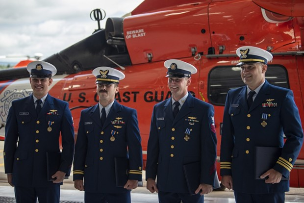 Coast Guard Air Station Humboldt Bay crew members Petty Officer 3rd Class Tyler Cook, an aviation maintenance technician, Lt.j.g. Adam Ownbey, a MH-65 Dolphin helicopter pilot, Petty Officer 1st Class Graham McGinnis, an aviation survival technician, Cmdr. Derek Schramel, a MH-65 Dolphin helicopter pilot, stand for a photo. - COAST GUARD PHOTO BY PETTY OFFICER 3RD CLASS TAYLOR BACON