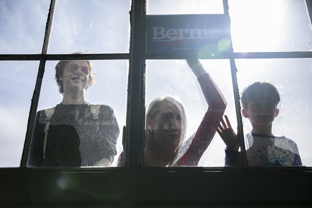 Supporters peer through the window during a Bernie Sanders presidential campaign event at Craneway Pavilion in Richmond, CA on February 17, 2020. - PHOTO BY ANNE WERNIKOFF FOR CALMATTERS