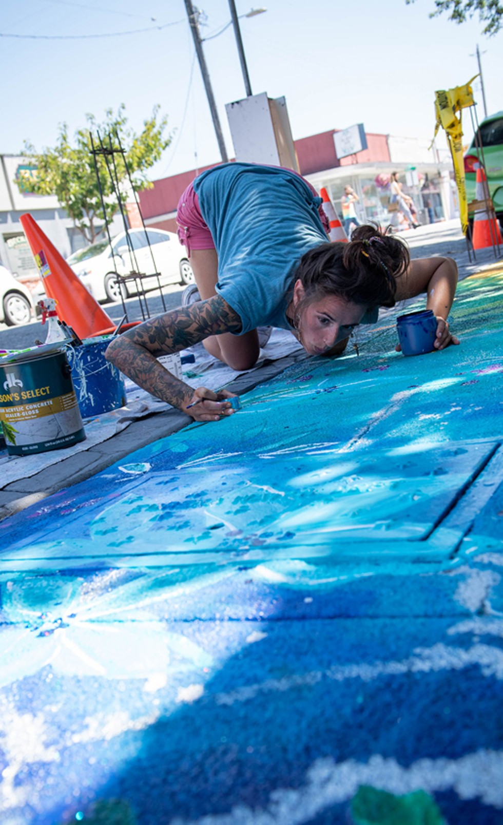 """Ashley Rose blows glitter into the paint of her work titled """"Complement in Chaos."""" - PHOTO BY MARK MCKENNA"""