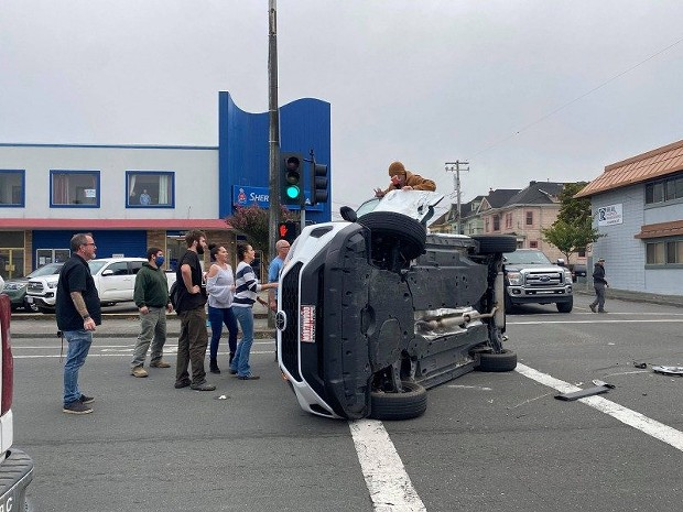 A man helping the driver getting out of a vehicle on its side. - MARK MCKENNA
