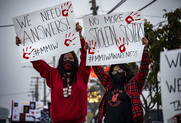 """Yvonne Guido (left) and Wakara Scott (right) stand holding signs reading """"We need answers!"""" and """"No more stolen sisters,"""" respectively at the Missing and Murdered Indigenous Peoples rally at the federal building in Fortuna. - KRIS NAGEL"""
