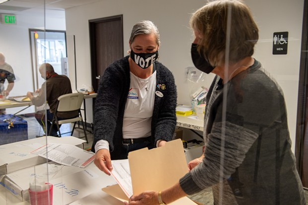 Poll worker Kristen Porter, left, places a ballot in a folder held by Julie Fulkerson at the Eureka Pentecostal Church on Hoover Street. Porter has worked several elections while Fulkerson was working her first at the polls. - MARK MCKENNA