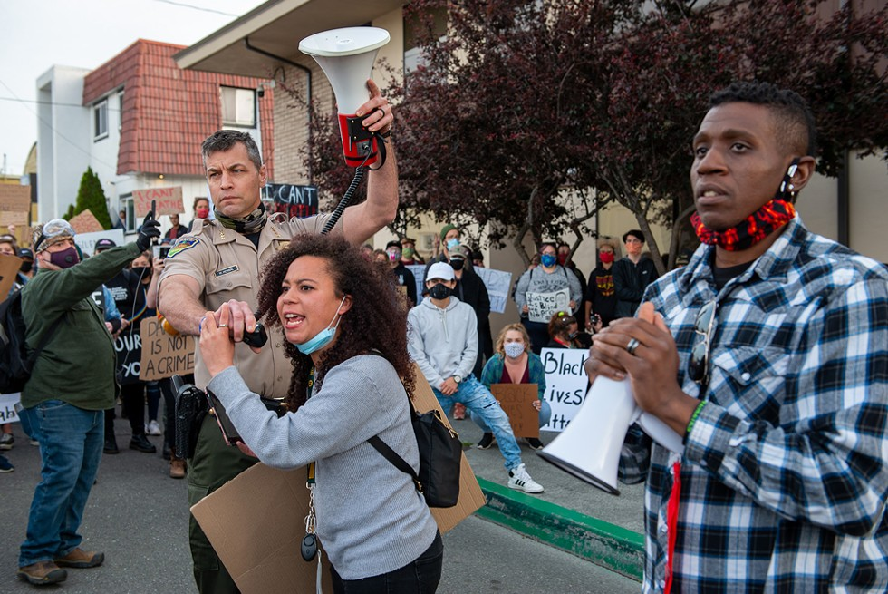 Humboldt County Sheriff William Honsal holds a microphone for protester Malia Haley as she addresses a crowd asking them to listen to what local law enforcement leaders had to say during a May 31 Black Lives Matter protest in Eureka. - MARK MCKENNA