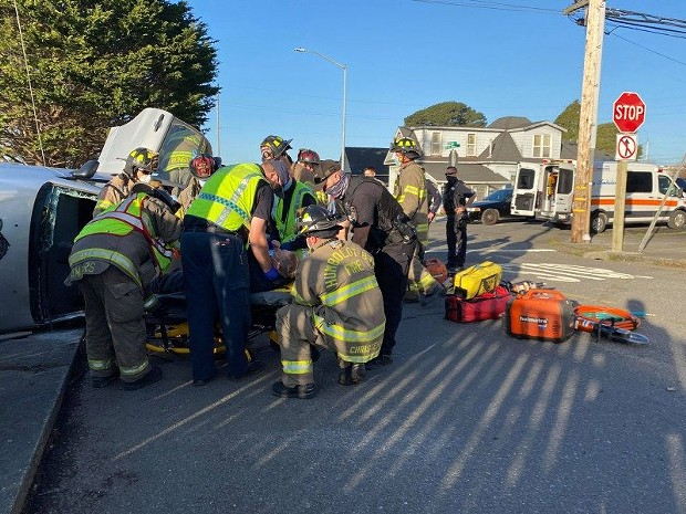 Emergency personnel gently lay the injured driver onto a stretcher. [All photos by Mark McKenna]
