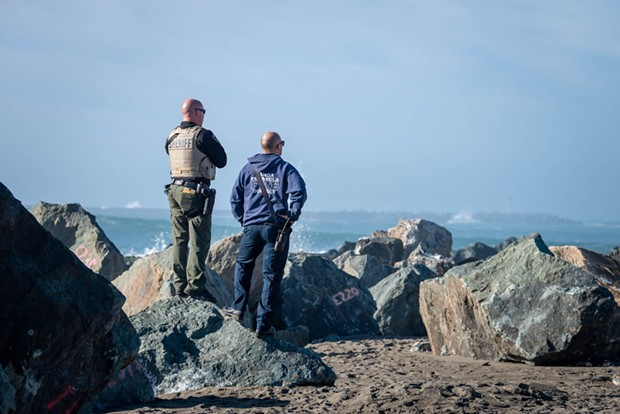 Searchers scour the surf during the search and rescue effort. - MARK MCKENNA