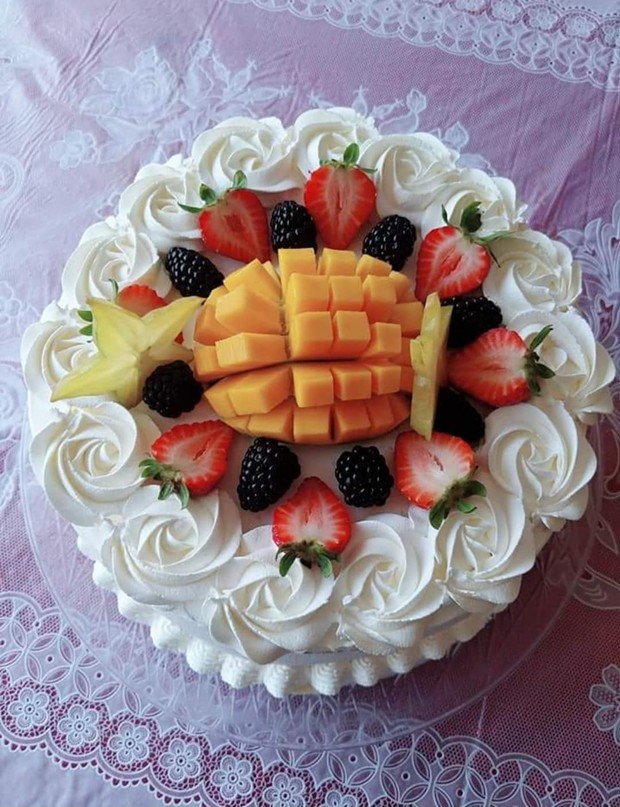 A mango-topped custom layer cake. - SUBMITTED