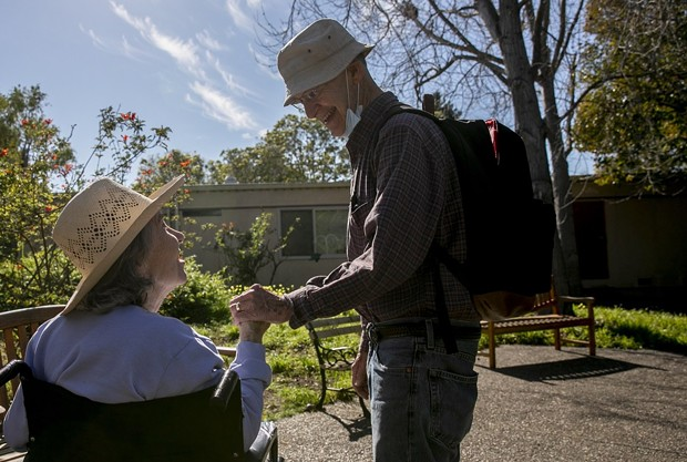 Larry Yabroff and his wife Mary greet each other during a visit at Chaparral House, a skilled nursing facility where Mary is a resident, in Berkeley on Feb. 25, 2021. Because both are vaccinated, the facility allows them to have non-socially distanced visits. Most California facilities, however, will not allow in-person visits. - PHOTO BY ANNE WERNIKOFF, CALMATTERS