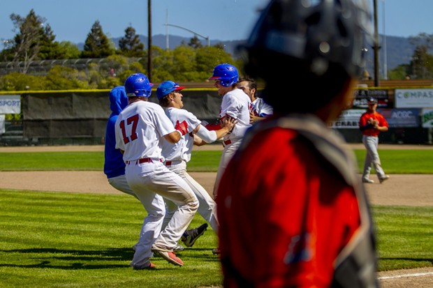 Teammates congratulate Crabs second baseman Ethan Fischel (#12) after he hit the game winning RBI in the bottom of the 13th inning to give the Humboldt Crabs their first series win of the season with a 5-4 win over the Lincoln Potters in the third game of the series at Arcata Ballpark as the Potters leave the field. - PHOTO BY THOMAS LAL