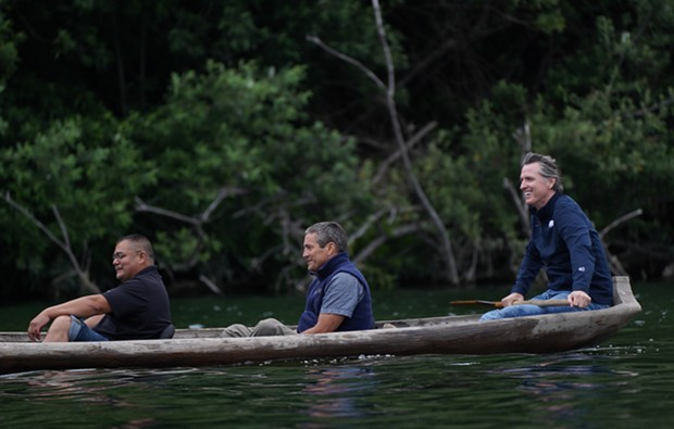 Yurok Chair Joseph L. James, California Natural Resources Secretary Wade Crowfoot and Gov. Gavin Newsom travel in a traditional redwood canoe down the Klamath River on the Yurok Reservation. - SUBMITTED