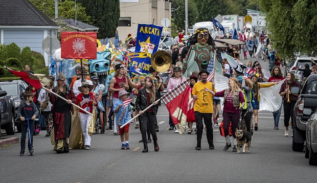 An eclectic mix of eager parade participants gathered in the Creamery District before walking to the plaza and making three loops around the square. - PHOTO BY MARK LARSON